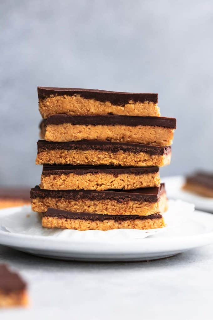stack of six no bake peanut butter bars on a plate with more bars surrounding on table