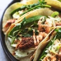 up close fish tacos with slaw and avocado slices on plate