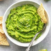 guacamole with spoon and tortilla chips dipped