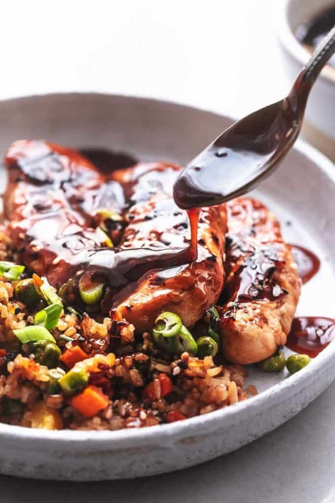 spoon drizzling sauce onto cooked chicken on plate with rice