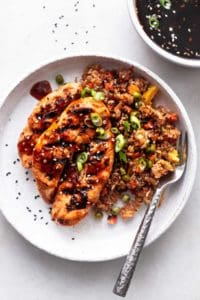 teriyaki chicken and rice with bowl of sauce on table