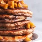 stack of apple cinnamon pancakes with apple topping and syrup