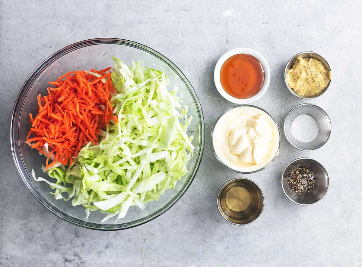 shredded cabbage and carrots in a bowl beside pinch bowls with ingredients