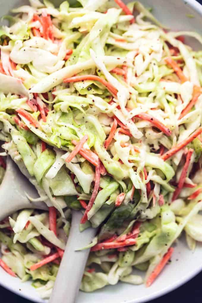 up close shredded cabbage and carrots tossed in creamy dressing