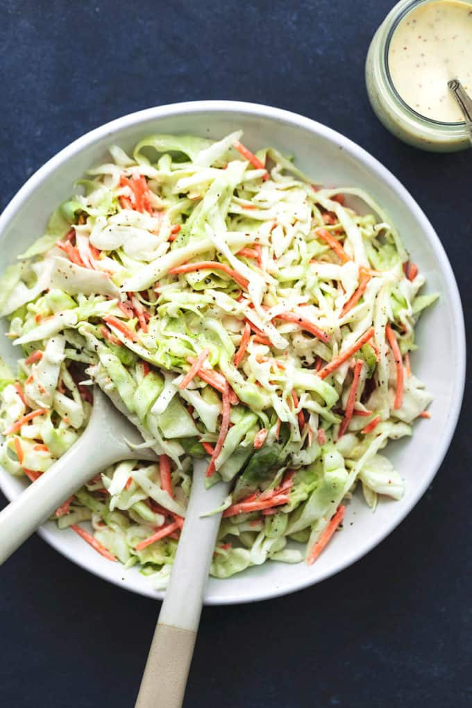 overhead view of coleslaw with serving spoons in platter and jar of sauce