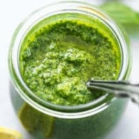 basil pesto sauce with spoon in glass jar with lemons and basil on table