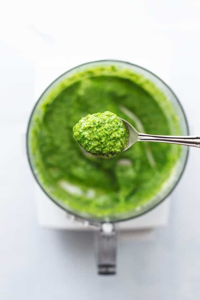 spoon of herb sauce above food processor