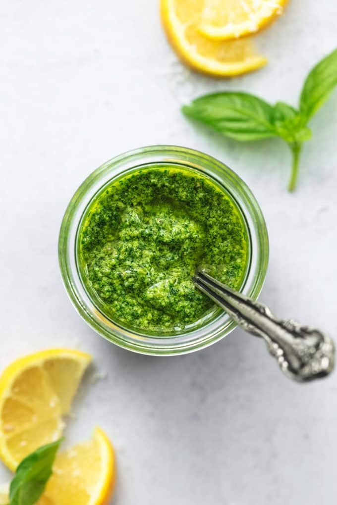 overhead view of jar of pesto with lemon wedges and basil leaves on table