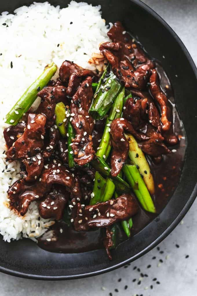 up close view of beef strips with green onions and rice topped with sesame seeds