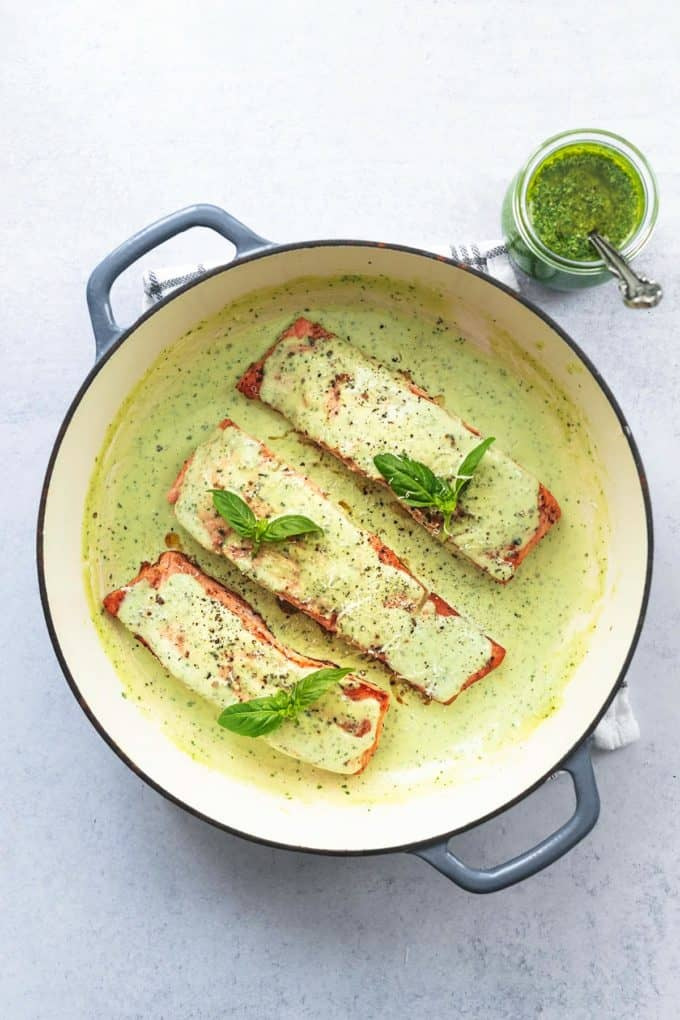 three salmon fillets in skillet with pesto sauce and sauce in jar