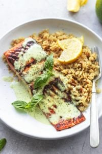 pesto salmon with orzo and lemon wedges on plate