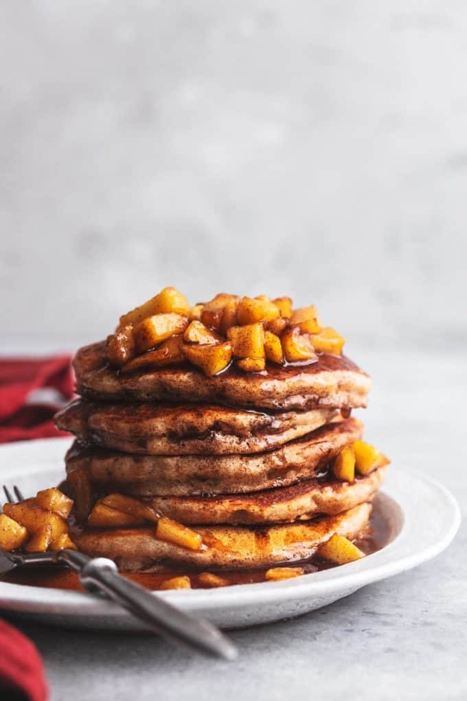 tabletop view of apple cinnamon pancakes stacked on plate with napkin to the side