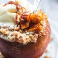 up close spoon digging into apple with filling and oat topping