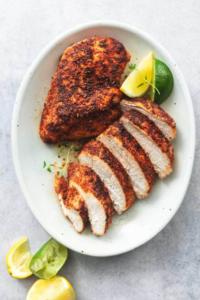 one whole and one sliced chicken breasts with lime wedges on platter