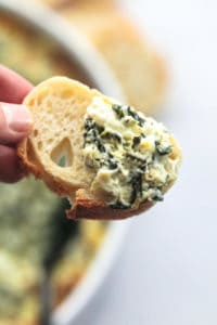 hand holding bread with spinach dip on it