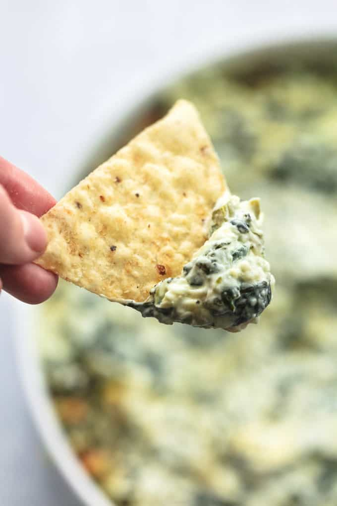 hand scooping tortilla chip into dip