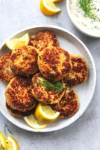 platter of crab cakes with lemon wedges and fresh dill