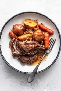 beef chunks with carrots and potatoes with gravy on plate with fork