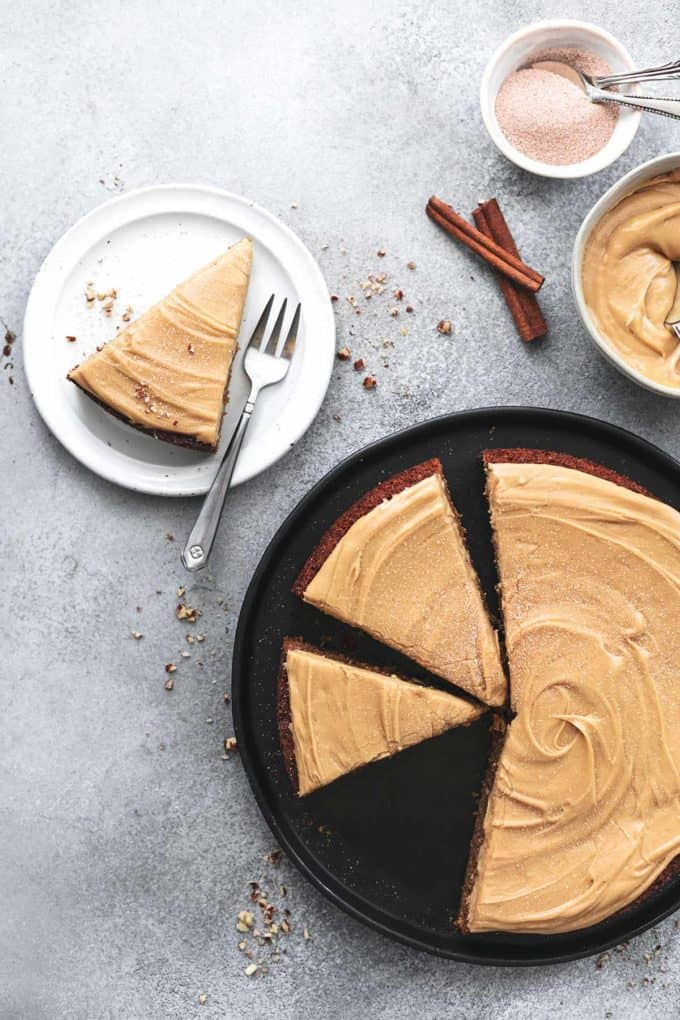 overhead view of spice cake with three slices and cinnamon sticks on table