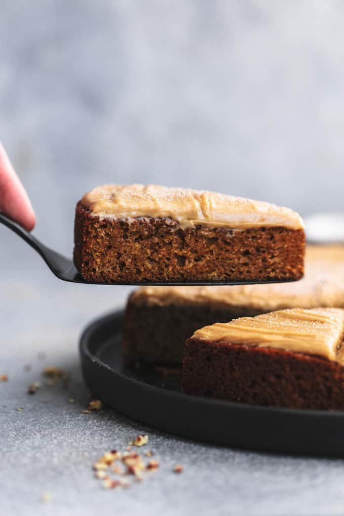 hand raising one slice of cake on a serving spatula from a platter